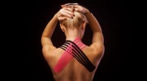 Medical taping op de bovenrug met zwarte en roze kinesiotape.
