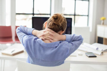 Een vrouw met een verhoogde spierspanning in haar nek achter een bureau.